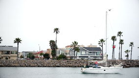 PORT HUENEME, CA U.S.A - JUNE 2015: Two men set sail out of harbor on overcast morning aboard sailboat. stock video footage