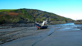 Port Isaac Harbor - Cornwall - Fishing Boat - Low Tide. Fishing boat on the sand during low tide in Port Isaac Harbor. This is the village where Doc Martin is Royalty Free Stock Image
