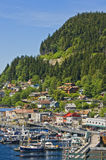 Port of Ketchikan, Alaska. Homes at the base of a mountain nestled in evergreen trees and a city street and small boat harbor, provide a backdrop for life on the royalty free stock photography