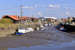 Port of Larros in France. Boats at low tide in the ostreicole harbor of Larros, commune is a located on the shore of Arcachon Bay, in the Gironde department in Royalty Free Stock Images