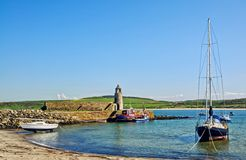 Port Logan, Dumfries and Galloway. Picturesque view of the beach with a lighthouse and boats at Port Logan, Dumfries and Galloway, on a beautiful summer day Royalty Free Stock Images
