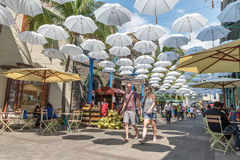 PORT LOUIS MAURITIUS - OKTOBER 03, 2015: Folket går på trottoaren Paraply ovanför huvudet louis mauritius port Fotografering för Bildbyråer