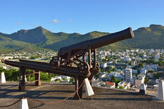 Port Louis. Old rusty cannon on background  of Port Louis,  the capital of Mauritius, Africa Royalty Free Stock Images