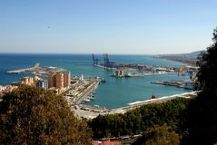 The port of Malaga in Spain between sea and sky trees. Photo made at the port of Malaga in Spain. In the photo, made from above, you see: the trees in the Stock Photos