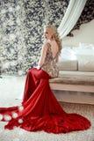 Port modèle de femme blonde élégante dans la robe rouge luxueuse avec le lon Photos libres de droits