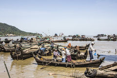 Port of Myeik. Boats are lying in the seaport of Myeik in the south of Myanmar. A small ferryboat comes in and is maneuvered by the sailor royalty free stock photos