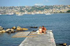 The port of Naples with boats and people getting tanned , Italy Royalty Free Stock Images