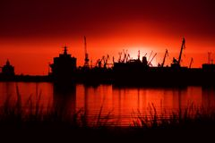 Port at night. View over the see on port at night, cranes on sunset light Royalty Free Stock Photos