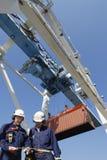 Port, ouvriers, grues et camions de conteneur Photos libres de droits