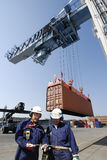 Port, ouvriers, grues et camions de conteneur Photographie stock