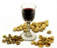 Port & Pistachios. Glass of port surrounded by pistachio nuts, some shelled, some in the shells, and empty shells royalty free stock photography