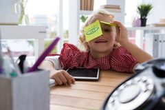 Port5rait of playful businesswoman with adhesive notes on eyes at office Stock Photography