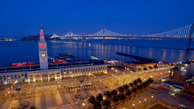 Port of San Francisco. Ferry Building and Bay Bridge illuminated at night in San Francisco, California Stock Photo