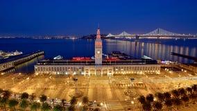 Port of San Francisco. Ferry Building and Bay Bridge illuminated at night in San Francisco, California Royalty Free Stock Photo