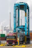Port shipping container truck trailer. ROTTERDAM, NETHERLANDS - SEP 6, 2013: Straddle carrier placing a shipping container on a truck trailer in a terminal of stock images
