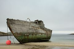 The Port Side of a Shipwrecked Boat. Close up of an old wooden shipwrecked boat run aground on a tan sandy beach on New Island in the Falkland Islands. A hot Stock Photography