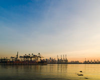 Port of Singapore. The tower cranes of a container port silhouetted and highlighted by the rising sun, in Singapore Stock Photography