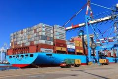 Port skeppsdockan med behållareskeppet och olika märken och färger av sändningsbehållare som staplas i en hållande plattform Arkivfoto