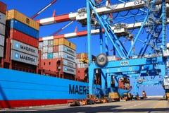 Port skeppsdockan med behållareskeppet och olika märken och färger av sändningsbehållare som staplas i en hållande plattform Arkivbilder