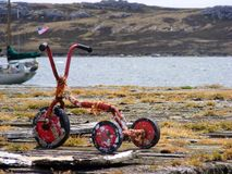 Toy scooter left out for some time on a pier - Falklands. Port Stanley, Falkland Islands, pier near Christchurch Cathedral Stock Image