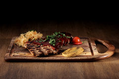 Port steak with red sauce. With braised cabbage, fresh cherry tometoes and mustard served on wooden board on rustic wooden counter Royalty Free Stock Photo