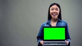 Port?til extremamente feliz da terra arrendada da mulher com tela verde, lucro grande em linha fotografia de stock