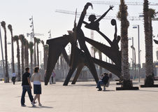 Port Vell, Barcelona. Walking people, palm trees and modern art sculpture on the Port Vell and Barceloneta Beach area in Barcelona, Spain; focus on palm trees Stock Photography