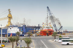 Port view with moored ships and workers, Saudi Arabia. RAS TANURA, SAUDI ARABIA - MAY 13, 2014: Port view with moored ships and workers, Saudi Arabia Royalty Free Stock Photos