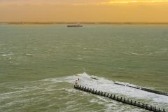 The port of vlissingen at sunset with a boat sailing by, landscape of a wild sea, Zeeland, The Netherlands stock photos