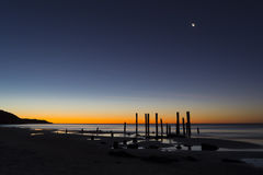 Port Willunga Beach, South Australia at Sunset with Moon on Show. The old jetty ruins on Port Willunga Beach, South Australia at sunset with the moon making it's Stock Photo