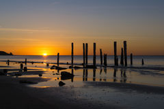 Port Willunga Beach, South Australia at sunset. The old jetty ruins on Port Willunga Beach, South Australia at sunset. Known as the sticks by locals and Royalty Free Stock Images