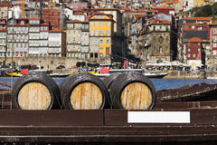 Port Wine barrels in a boat in the Douro River with the city of Porto in the background Royalty Free Stock Image