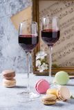Port wine with french dessert macaroons. Two glasses of port wine with variety of colorful french dessert macaron macaroons with different fillings served with Royalty Free Stock Image