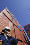 Port worker and containers. Port and dock worker with stacks of cargo containers in background Royalty Free Stock Image