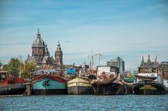 Port z ośniedziałymi cumującymi statkami w kanałowym i pogodnym niebieskim niebie w Amsterdam zdjęcie stock