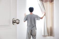 Porta aberta à sala, com uma cortina aberta do homem que recebe a luz solar na manhã Imagem de Stock Royalty Free