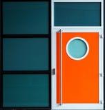 Porta alaranjada moderna do metal com janela da vigia Foto de Stock