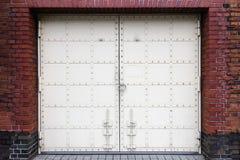 Porta antiga branca do ferro com o fechamento no fundo a da parede de tijolo vermelho Imagens de Stock