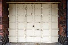 Porta antiga branca do ferro com o fechamento no fundo da parede de tijolo vermelho Imagem de Stock Royalty Free