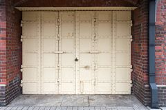 Porta antiga branca do ferro com o fechamento no fundo a da parede de tijolo vermelho Imagem de Stock