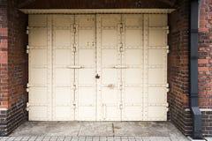 Porta antiga branca do ferro com o fechamento no fundo da parede de tijolo vermelho Imagens de Stock