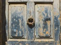 Porta azul antiga com um fundo oxidado do botão do anel do metal imagens de stock royalty free