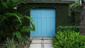 Porta azul da porta a um jardim Imagens de Stock Royalty Free