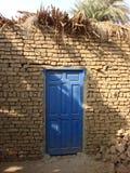 Porta azul na parede de tijolo da lama Imagens de Stock Royalty Free