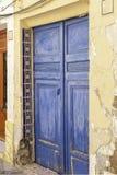 Porta azul pintada velha da madeira e de azulejos resistidos em uma parede velha do emplastro na Espanha imagens de stock royalty free