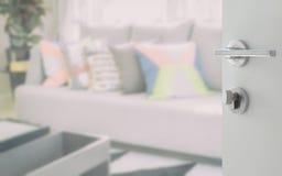 Porta bianca aperta a progettazione moderna del salone con i cuscini variopinti Immagini Stock