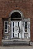 Porta bianca elegante e stagionata con i dettagli decorati sul muro di mattoni rustico fotografie stock
