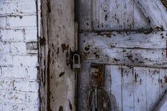 Porta bloccata di una tettoia di legno con la pelatura della pittura bianca fotografie stock libere da diritti