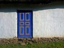 Porta blu rustica sulla parete bianca con il fondamento di pietra Fotografia Stock