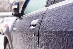 Porta, botão, buraco da fechadura do carro coberto com a neve e gelo após uma queda de neve imagem de stock